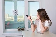妇女与机器人擦净剂的清洁窗口 库存图片