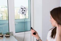 妇女与机器人擦净剂的清洁窗口 免版税图库摄影