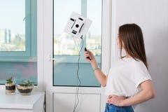 妇女与机器人擦净剂的清洁窗口 库存照片