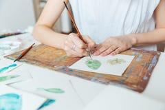 妇女与油漆刷和水彩油漆的艺术家绘画的手 库存图片