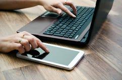 妇女与片剂和膝上型计算机一起使用 免版税图库摄影