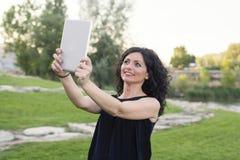 妇女与片剂的mkes selfie 库存图片