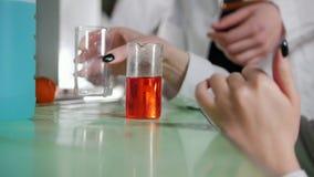 妇女与白色混合橙色液体在医学实验室 影视素材