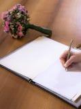 妇女与笔的手文字在与textspace copyspace婚礼花花束的书 免版税库存照片