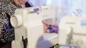 妇女与缝纫机一起使用 缝纫机和overlock机器 股票录像