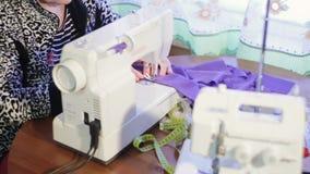 妇女与缝纫机一起使用 缝纫机和overlock机器 股票视频
