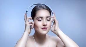 妇女与耳机的秀丽画象 图库摄影