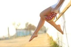 妇女与脚跟垂悬的腿剪影她的手 免版税图库摄影