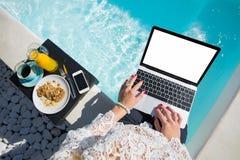 妇女与膝上型计算机一起使用在室外浴缸旁边 库存图片