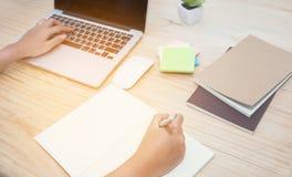 妇女与膝上型计算机和笔记本一起使用 免版税库存照片