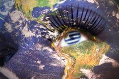 妇女与行星地球纹理的` s面孔和在眼睛里面的乌拉圭旗子 免版税图库摄影