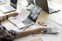 妇女与计算器、没有的商业文件和的计算机一起使用 库存图片