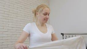 妇女与铁的主妇冲程白色衬衫和舞蹈在她的手上 股票视频
