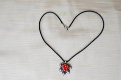妇女与银色垂饰的` s项链与以心脏的形式红色圈子对天圣华伦泰由黑螺纹制成 库存图片