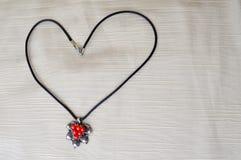 妇女与银色垂饰的` s项链与以心脏的形式红色圈子对天圣华伦泰由黑螺纹制成 免版税库存照片