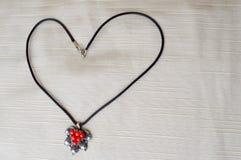 妇女与银色垂饰的` s项链与以心脏的形式红色圈子对天圣华伦泰由黑螺纹制成 图库摄影