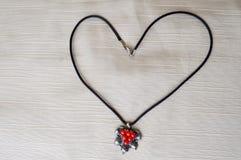 妇女与银色垂饰的` s项链与以心脏的形式红色圈子由黑螺纹制成 库存照片