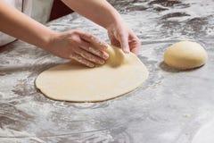 妇女与面团一起使用在面包店,在从钢的一张桌上 库存图片