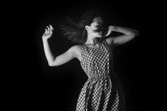 妇女丝毫长的头发的黑白色照片在一件夏天礼服的在黑背景 库存照片