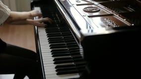 妇女两手演奏在大平台钢琴关闭的古典音乐在慢动作 股票录像