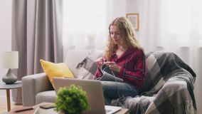 妇女中景坐沙发和编织的钩针编织衣裳在舒适家 股票视频