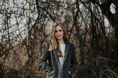 妇女中景画象看在分支背景的冬天外套的照相机 库存照片