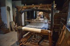 妇女为一台老纺丝机工作 库存图片