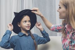 妇女为万圣夜帮助一个女孩拾起一个黑巫婆帽子 库存照片