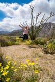 妇女为喜悦跳在蜡烛木植物仙人掌旁边 在照片的野花 免版税图库摄影