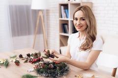 妇女为圣诞节假日做首饰 女孩参与花圈制造  库存照片
