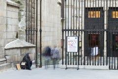 妇女为施舍乞求在入口到城市教会 库存照片