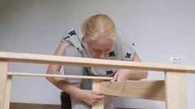 妇女主妇在屋子里坐地板,收集木机架,买在商店 家具装配  股票录像