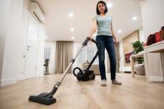 妇女主妇或佣人或者hoovering与在明亮的豪华公寓的吸尘器的服务工作者广角照片  库存照片