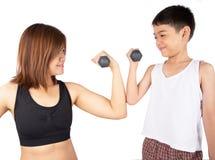 妇女举的哑铃制定出重量训练得到强和取消油脂与儿子 免版税库存图片