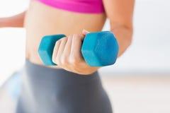 妇女举的哑铃重量的中间部分在健身房的 库存图片