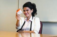 妇女举行一个房子模型在办公室 免版税库存照片