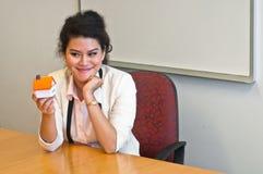 妇女举行一个房子模型在她的办公室 免版税库存照片