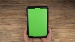 妇女举行与一个绿色屏幕的一平板电脑您自己的习惯内容的 股票录像
