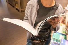 妇女举行书在手中在图书馆里 库存图片