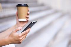 妇女举行咖啡和巧妙的电话在街道上,有空间的文本的 免版税库存图片