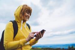 妇女举行在女性手小配件技术的,backgroundblu天空的旅游少女使用流动智能手机,微笑徒步旅行者enjo 库存图片