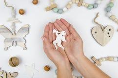 妇女举行天使在白色背景的手上与木蝴蝶、小珠、榛子坚果和心脏, Flatlay 免版税库存图片