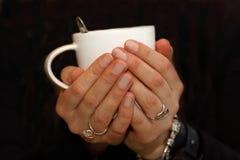 妇女举行每温暖的咖啡 图库摄影