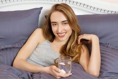 妇女举行水玻璃,在床上 女孩感受宿酒 拿着杯水的亚裔白人妇女的关闭 r 库存图片