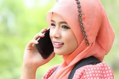 妇女举行谈话的智能手机电话与朋友 图库摄影