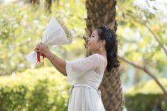 妇女举行高兴花束的花敬佩 免版税库存图片
