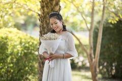 妇女举行高兴花束的花敬佩 免版税库存照片