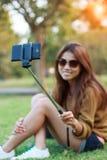 妇女举行monopod用途巧妙的电话在公园采取照片selfie 免版税库存图片