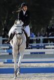 妇女乘坐的白马在跳跃的竞争时 库存图片