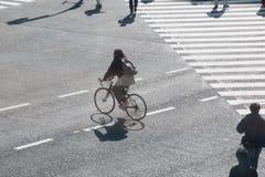 妇女乘驾剪影横跨街道的自行车 免版税库存照片